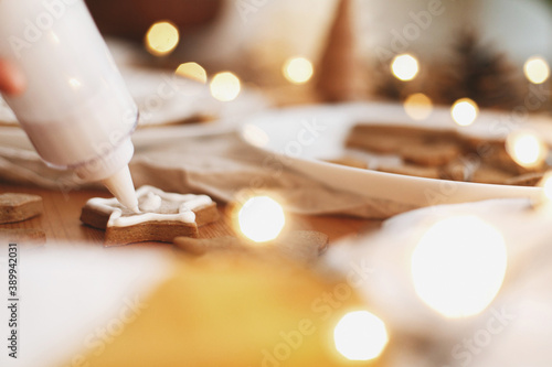 Decorating gingerbread star cookie with icing on  table with lights Fototapet