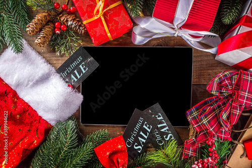 Christmas Sale Concept. Black friday, Green or Cyber Monday background with Laptop, Tablet, Christmas Decor and Gift Boxes, wooden background top view copy space
