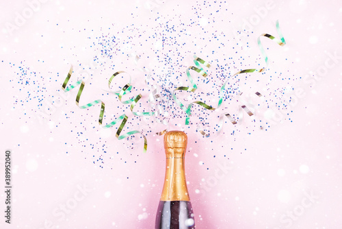 New Year's serpentine flies out of the bottle of champagne, multicolored sequins on a light background Fototapeta