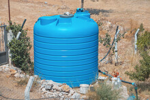 A Large Blue Water Tank Near A Private Farm Or Garden In A Dry Area. Concept Of Equipment For Agriculture And Drought