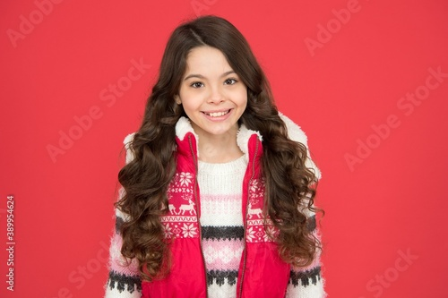 Photo cheerful kid has beautiful hairstyle in warm winter clothing on new year holiday