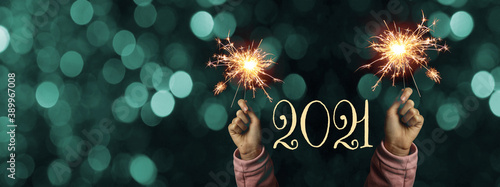 Obraz Happy New Year 2021 background banner panorama - Happy girl hold sparkling sparklers in her hands at dark night with turquoise bokeh lights - fototapety do salonu