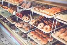 A View Of A Glass Display Of Donuts At A Local Donut Shop.