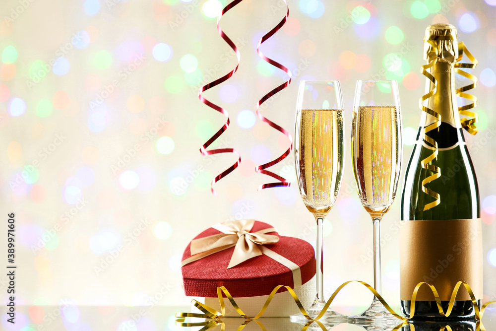 Fototapeta Bottle and glasses of champagne with gift box on blurred lights background