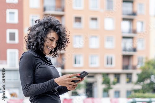 Fotografie, Obraz Closeup shot of a Spanish woman smiling while using her phone on a blurred backg
