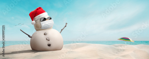 Obraz Concept: sand snowman wearing sunglasses, Santa hat and mask during coronavirus pandemic on sunny Christmas day afternoon COVID-19 - fototapety do salonu
