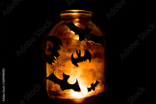 Fotografering There is a candle in a transparent glass jar, a close-up of black bats for Halloween are glued to the jar in a dark spooky room