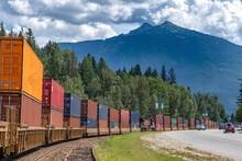 Cargo Train On Track Through A Mountain Town
