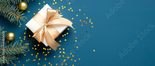 Obraz Christmas gift box with golden ribbon bow, fir branches, confetti on dark blue background. Xmas banner design, header mockup. Flat lay, top view, copy space. - fototapety do salonu
