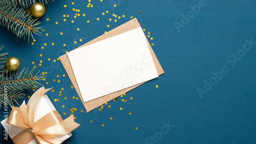 Foto Christmas letter envelope with blank paper card, white gift box with golden ribbon bow, fir branches decorated balls on dark blue background