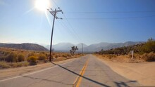 Driving Towards The Mountains Along A Desert Road With The Sun High In The Sky - Point Of View