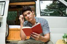 Man Reading A Book Near CV Car...