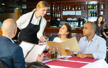 Young Smiling Waitress Consulting Guests Choosing Drinks And Meals In Cozy Pizzeria