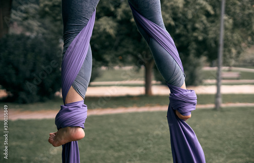 Young Caucasian woman doing aerial yoga with hammocks in the park Fototapet
