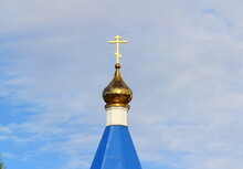 Orthodox Christian Church With Blue Roof, Golden Dome And Cross In Russia. A Building For Religious Ceremonies With A Bell Tower Against A Cloudy Sky