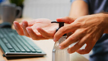 Close Up Of Man Using Hand Sanitizer Sanitiser While Working In Office Room. Entrepreneur In New Normal Company Office Workplace Cleaning Disinfecting Hands Using Alcohol Gel Against Corona Virus.