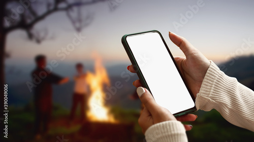 Obraz Female tourist hands holding smartphone and rest at night camping in the mountains beside campfire. - fototapety do salonu