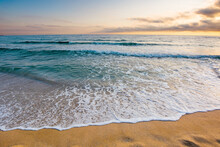 Sunrise At The Sea. Beautiful Summer Landscape On The Sandy Beach. Green Waves Rush On The Shore In Golden Light