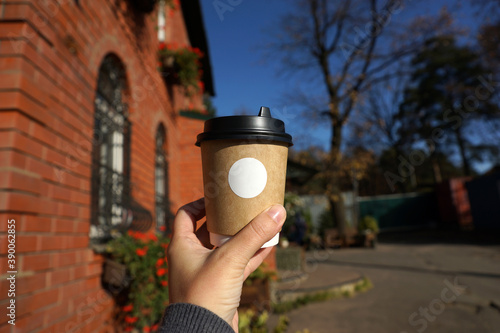 A woman's hand holds a drink in a paper cup against the background of a brick bu Fototapet
