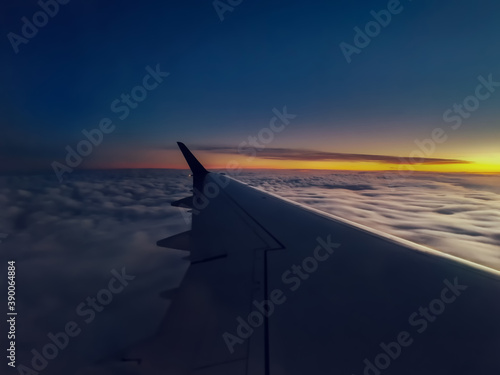 Wing of a plane flying above the cloudy sky during the sunset - perfect for wallpapers