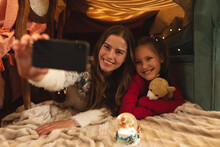 Caucasian Woman And Her Daughter Smiling And Taking Selfie With Smartphone