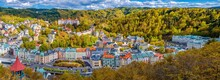 Karlovy Vary City Aerial Panoramic View With Row Of Colorful Multicolored Buildings And Spa Hotels In Historical City Centre. Panorama Of Karlsbad Town And Slavkov Forest Mountains In Autumn
