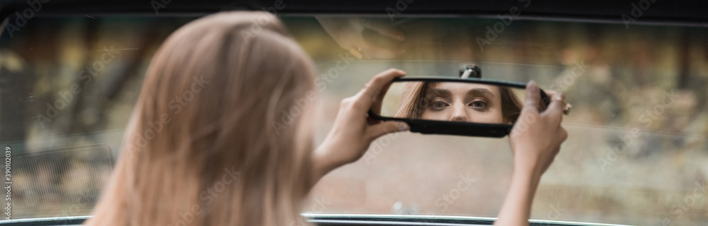Fototapeta back view of young woman adjusting rearview mirror in car on blurred foreground, banner