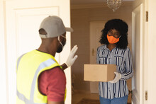 Delivery Man Wearing Face Mask Delivering Package To Woman Wearing Face Mask At Home