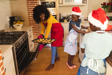 African American Mother Wearing Apron Holding Baked Cookies And Daughter And Son Wearing Santa Hat B