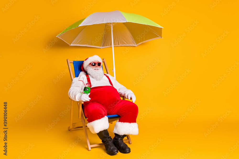 Fototapeta Full body photo of grey white hair bearded santa claus chill chaise-lounge hold cocktail x-mas christmas eve noel time rest wear hat pants boots isolated bright shine color background