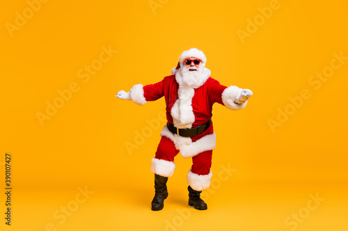 Full size photo of funky santa claus with grey beard listen x-mas christmas music song headset dance wear sunglass headwear cap isolated over bright shine color background
