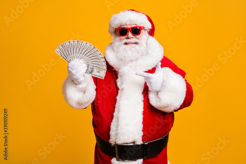 Fototapeta Portrait of his he nice attractive cheerful confident fat overweight bearded Santa holding in hand demonstrating usd cash budget isolated bright vivid shine vibrant yellow color background obraz