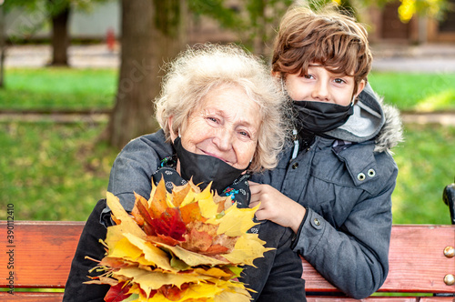 Happy teenager boy in a black mask presented an elderly woman a bouquet of fallen leaves outdoors in autumn park Fototapet