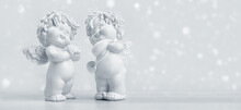 Two Adorable Toy Cherub Baby Angels On A Snowy Christmas Day. White Christmas Concept. Seasons Greetings Card Or Banner With Copy Space