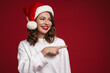 Happy cheery young woman in christmas santa hat