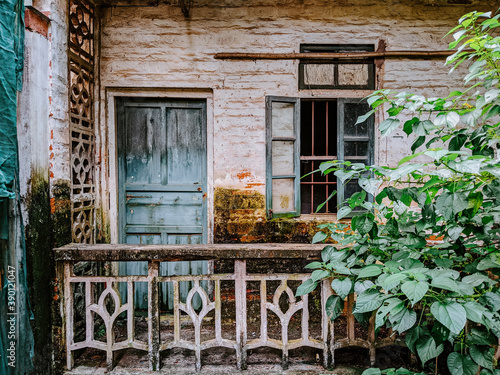 Terrace of an old house with a weathered door and window © Wirestock
