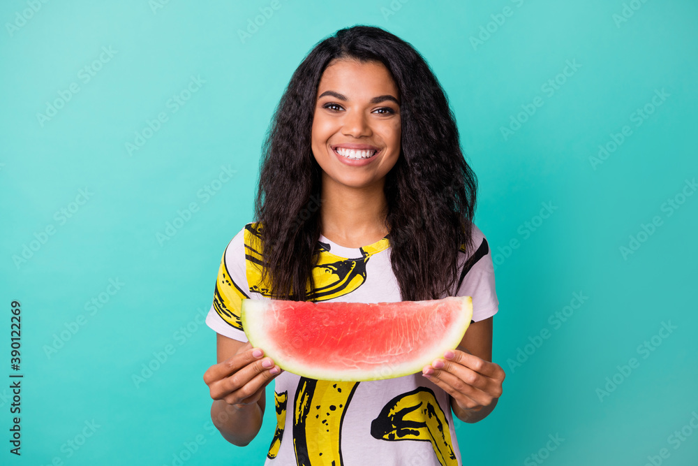 Fototapeta Photo of positive afro american girl hold watermelon tasty slice wear pink t-shirt isolated on teal color background