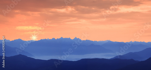 mountain landscape panorama at sunset - blue shimmering mountain tops with orange evening sky #390139404