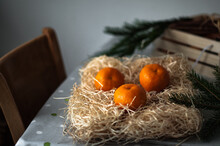 Three Mandarins On Straw Shavings On The Table In The Daylight.