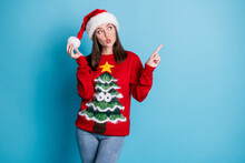 Photo Of Lovely Pretty Lady Direct Indicate Finger Look Up Empty Space Play Pompom Wear Santa X-mas Headwear Red Ornamented Sweater Jeans Isolated Blue Color Background