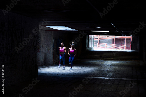 Fotografia, Obraz Caucasian female twins jogging in an underground passage