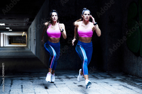 Foto Caucasian female twins jogging in an underground passage