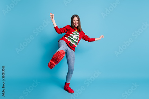Full length body size photo of funny demale student playing fooling standing on one leg laughing showing red shoe wearing xmas sweater isolated on blue color background