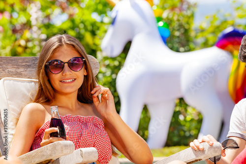 Canvas Cute teen girl with soda bottle smile and wearing sunglasses sit on deck chair i