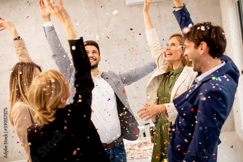 Group of business people celebrating and toasting with confetti falling in the office