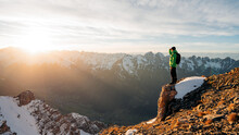 Climber Looking At A Snowy Mountain Landscape In A Sunny Winter Day. Travel Man Tourist Alone On The Edge Cliff Mountains And Looking On The Valley. Adventure Lifestyle Extreme Vacations.