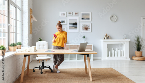 creative young woman designer in a yellow sweater in the workplace at home in interior of  apartment with large windows.