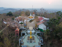 Nan / Thailand -February 2020 : Wat Phra That Khao Noi Temple In Northern Thailand With A Large Golden Standing Buddha Statue Over Looking The City From The Mountain Top In Sunset