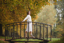 Young Woman In White Cozy Sweater On Bridge At Natural Park In Autumn Day.