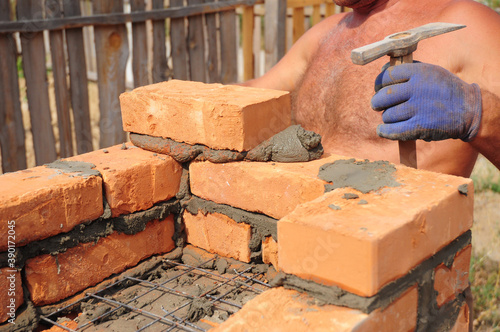 Obraz na plátně A mason person is laying a brick house wall with reinforced mesh, wire using a trowel and a masonry hammer